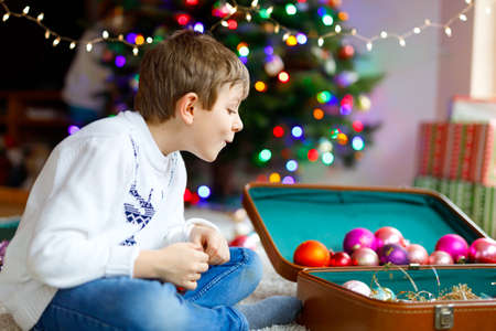 Beautiful kid boy and colorful vintage xmas toys and ball in old suitcase. Foto de archivo