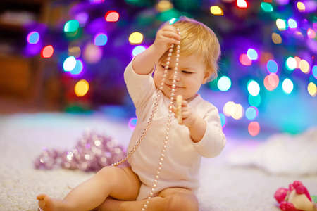Adorable baby girl holding colorful lights garland in cute hands. Little child in festive clothes decorating Christmas tree with family. First celebration of traditional holiday called Weihnachten