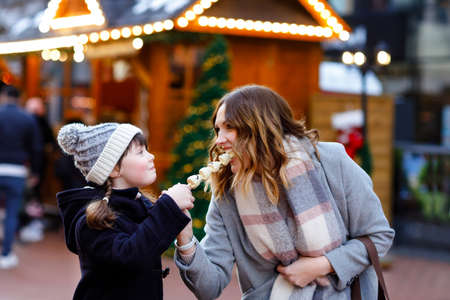 Mother and daughter eating white chocolate covered fruits and strawberry on skewer on traditional German Christmas market. Happy girl and woman on traditional family market in Germany during snowy day