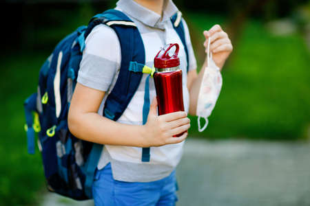 Closeup of kid boy, medical mask, water bottle and backpack or satchel. Schoolkid on way to school. child outdoors. Back to school after quarantine time from corona pandemic disease lockdown. no face.