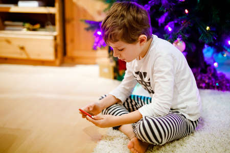 Cute little blond kid boy using smartphone on Christmas with decorated tree on background. Happy healthy hild having fun at home. Popular gift for xmas