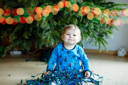 Cute baby girl taking down holiday decorations from Christmas tree. child holding light garland. Family after celebration remove and dispose tree