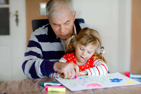 Cute little baby toddler girl and handsome senior grandfather painting with colorful felt pens and pencils at home. Grandchild and man having fun together, creative family.