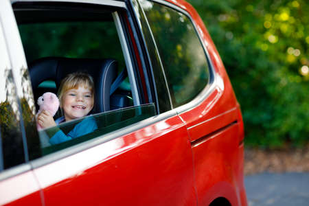 Adorable toddler girl sitting in car seat, holding plush soft toy and looking out of the window on nature and traffic. Little kid traveling by car. Child safety on the road. Family trip and vacations