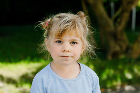 Portrait of adorable cute toddler girl of three years. Beautiful baby with blond hairs looking and smiling at the camera. Happy healthy child. Stockfoto