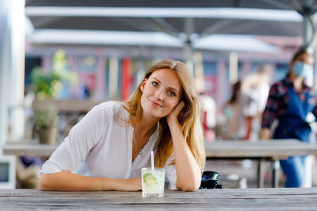 Young woman drinking mojito cocktail at cafe terrace at hot summer day. Beautiful businesswoman enjoying warm evening at afterwork restaurant. Happy smiling alone lady. Фото со стока