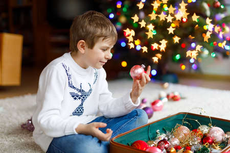 Beautiful kid boy and colorful vintage xmas toys and balls. Child decorating Christmas tree