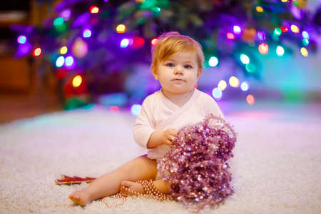 Adorable baby girl holding colorful lights garland in cute hands. Little child in festive clothes decorating Christmas tree with family. First celebration of traditional holiday called Weihnachten Stock Photo