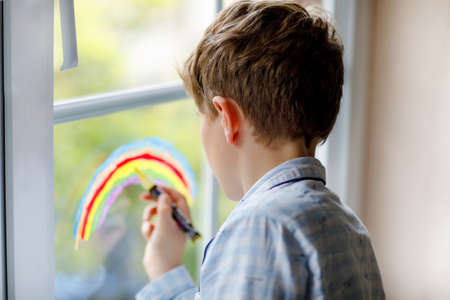 Lovely school kid boy in pajamas painting rainbow with colorful window color during pandemic quarantine. Children painting rainbows around the world with the words Lets all be well.
