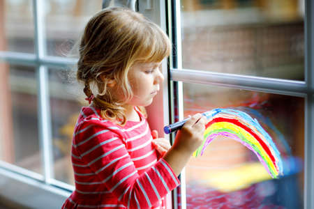 Adoralbe little toddler girl with rainbow painted with colorful window color during pandemic quarantine. Child painting rainbows and hearts around the world with words Lets all be well.