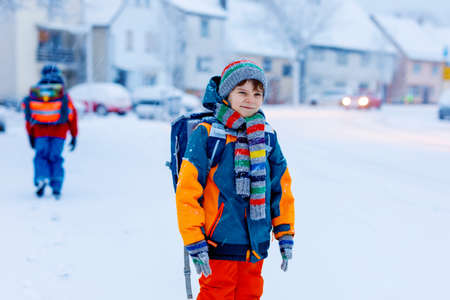 Two little kids boys of elementary class walking to school during snowfall