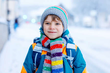 Gorgeous little school kid boy of elementary class walking to school during strong snowfall. Early morning and snowy streets in city. Child with backpack or satchel in colorful winter clothes