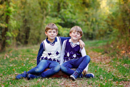 Portrait of little school kids boys sitting in forest. Happy children, best friends and siblings having fun on warm sunny day early autumn. Twins and family, nature and active leisure. 写真素材