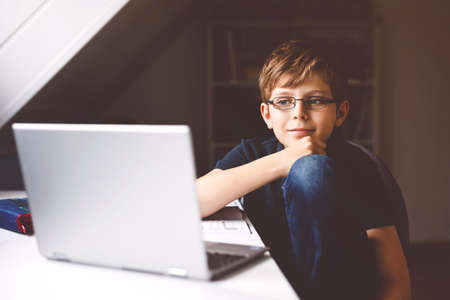 Kid boy with glasses learning at home on laptop for school. Adorable child making homework and using notebook and modern gadgets. Home schooling concept. 免版税图像