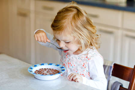 Adorable toddler girl eating healthy cereal with milk for breakfast. Cute happy baby child in colorful clothes sitting in kitchen and having fun with preparing oats, cereals. Indoors at home