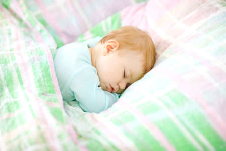 Adorable little baby girl sleeping in bed. Calm peaceful child dreaming during day sleep. Beautiful baby in parents bed. Sleeping together concept.