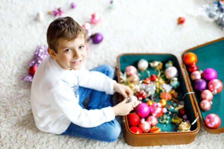 Beautiful kid boy and colorful vintage xmas toys and ball in old suitcase. Child decorating Christmas tree