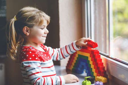Cute little toddler girl by window create rainbow with colorful plastic blocks during pandemic coronavirus quarantine. Children made and paint rainbows around the world as sign.