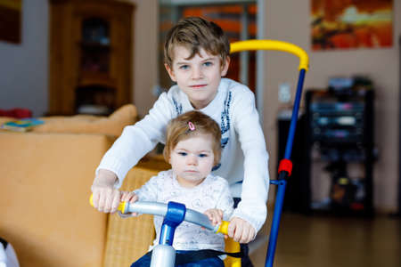 Little kid boy pushing bycicle or tricycle with cute baby sister. Toddler girl and brother playing together at home, indoors. Siblings bonding and love, jointly and common activity and game.