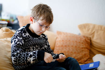 Tired little kid boy with glasses at home making homework at the morning before the school starts. Little child learning multiplication tables basics indoors. Home schooling during corona virus time Archivio Fotografico