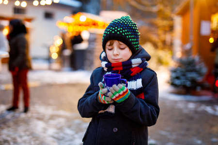 Little cute kid boy drinking hot children punch or chocolate on German Christmas market. Happy child on traditional family market in Germany, Laughing boy in colorful winter clothes