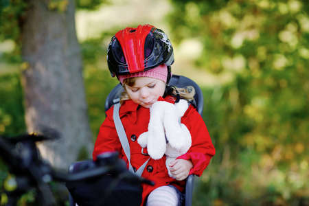 Little toddler girl with security helmet on head sitting in bike seat of her mother or father bicycle. Safe and child protection concept. Family ctivity trip on autumn day. Kid holding push soft toy