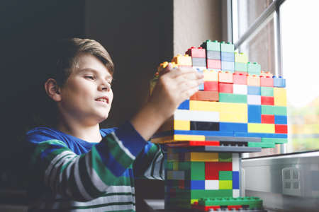 Little kid boy playing with lots of colorful plastic blocks. Adorable school child having fun with building and creating building by window. Creative leisure technic and robotic during corona time