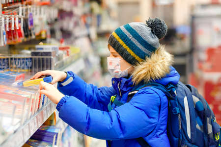 Little kid boy wearing medical mask buy school stuff in supermarket. Child with backpack and winter clothes. Schoolkid buying pencils. Lockdown and quarantine time during corona pandemic disease