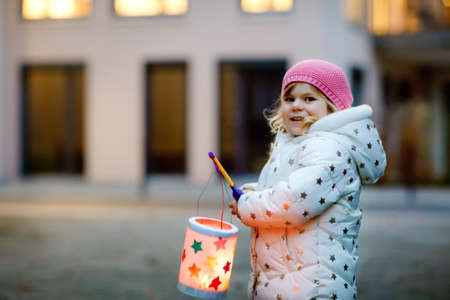 Little kid girl holding selfmade lanterns with candle for St. Martin procession. Healthy cute toddler child happy about children and family parade in kindergarten. German tradition Martinsumzug