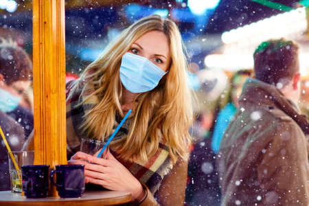 Woman with medical mask on German Christmas market. People with masks as protection against corona virus. Covid pandemic time in Europe and in the world Stockfoto