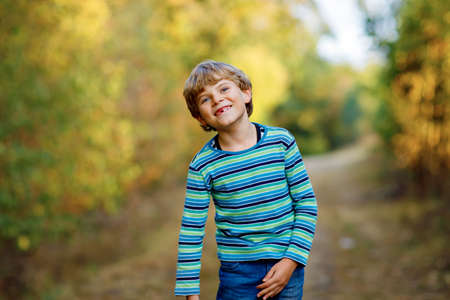 Portrait of little cool kid boy in forest. Happy healthy child having fun on warm sunny day early autumn. Family, nature, love and active leisure. Stockfoto