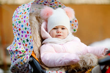 Sad crying hungry baby girl sitting in the pram or stroller on cold autumn, winter or spring day. Weeping child in warm clothes, fashion stylish baby coat and hat. Snow falling down 스톡 콘텐츠