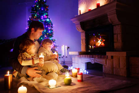 Father and two little toddler boys sitting by chimney, candles and fireplace and looking on fire. Family celebrating Christmas. With Xmas tree and lights on background. Kids happy about gifts