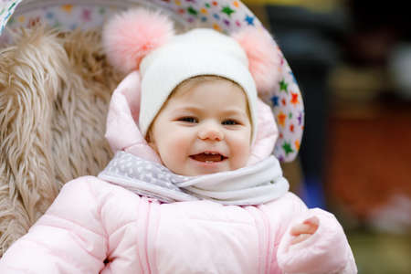 Cute little beautiful baby girl sitting in the pram or stroller on cold autumn, winter or spring day. Happy smiling child in warm clothes, fashion stylish baby coat and hat. Snow falling down