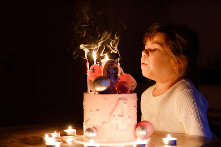 Adorable little toddler girl celebrating fourth birthday. Cute toddler child with homemade princess cake, indoor. Happy healthy toddler blowing 4 candles on cake