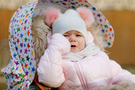 Sad crying hungry baby girl sitting in the pram or stroller on cold autumn, winter or spring day. Weeping child in warm clothes, fashion stylish baby coat and hat. Snow falling down
