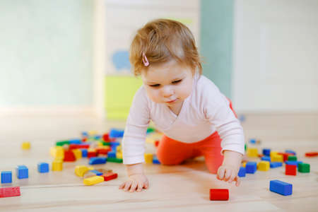 Cute little baby girl playing with educational toys. Happy healthy child having fun with colorful different wooden blocks at home or nursery. Baby crawling and learning colors and forms, indoors Reklamní fotografie