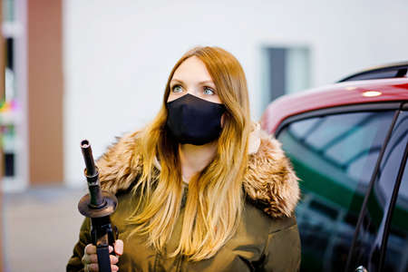 Woman wear medical mask at self-service gas station, hold fuel nozzle, refuel the car with petrol during corona virus pandemic lockdown. People in masks as preventive measure and covid protection