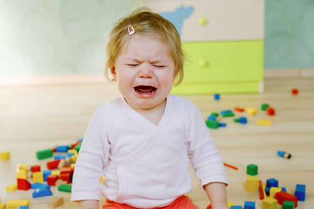 Upset crying baby girl with educational toys. Sad tired or hungry alone healthy child sitting near colorful different wooden blocks at home or nursery. Baby missing mother in daycare
