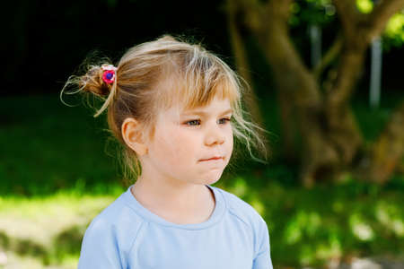 Portrait of adorable cute toddler girl of three years. Beautiful baby with blond hairs looking and smiling at the camera. Happy healthy child.