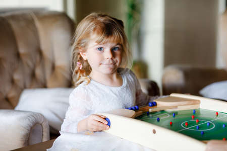 Happy little toddler girl playing table soccer with family at home. Smiling child having fun with board football, indoors. Indoor leisure for kids during corona virus self-isolation quarantine time.