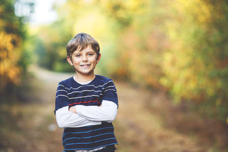 Portrait of little cool kid boy in forest. Happy healthy child having fun on warm sunny day early autumn. Family, nature, love and active leisure. 写真素材
