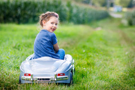Little preschool kid girl driving big toy car and having fun with driving in nature