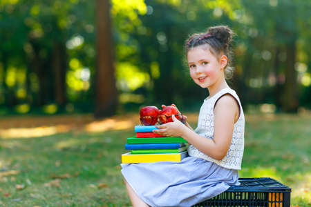 Happy adorable little kid girl reading book and holding different colorful books on first day to school or nursery. Child outdoors , Back to school concept. Healthy child of elementary class.