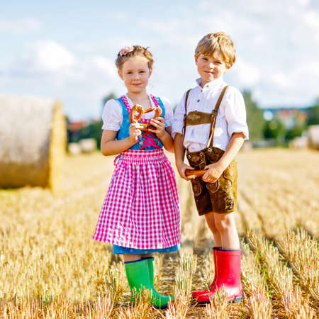 Two kids in traditional Bavarian costumes in wheat field. German children eating bread and pretzel during Oktoberfest. Boy and girl play at hay bales during summer harvest time in Germany.