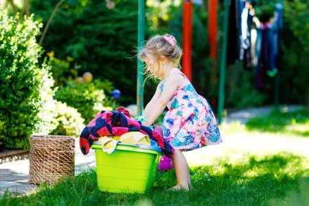 Toddler girl hanging clothes, fresh clean dresses and trousers for drying in garden, outdoors after making laundry. Happy child helping in household. Family working together, kid learning to help.