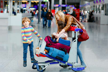 Two little kids, boy and girl, siblings and mother at the airport. Children, family traveling, going on vacation by plane and waiting on trolley with suitcases pushing by woman at terminal for flight.