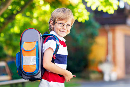 Happy little kid boy with glasses and backpack or satchel on his first day to school or nursery. Child outdoors on warm sunny day, Back to school concept. Standard-Bild