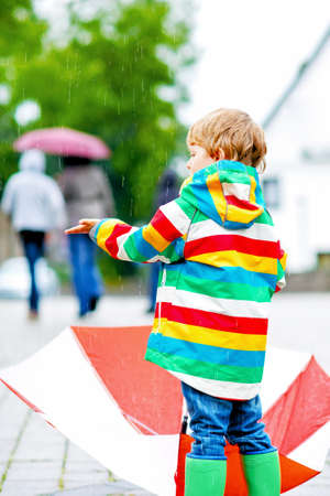 Little blond kid boy walking with big umbrella outdoors on rainy day. Child having fun with rain drops and wearing colorful waterproof clothes and boots Imagens