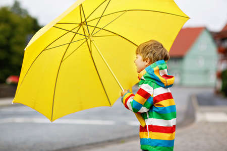 Little toddler boy playing with big yellow umbrella on rainy day. Happy positive child running through rain and puddles. Kid with rain clothes and rubber boots. Children activity on bad weather day. Imagens